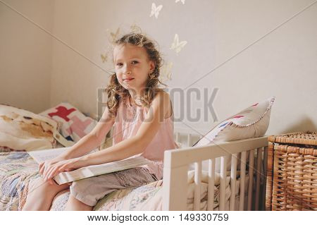 kid girl sitting on bed and reading book in her room. Cozy weekend at home lifestyle capture