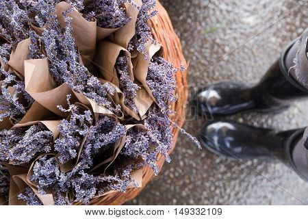 Top view on woman's legs in grey rubber boot standing close to a basket with beautiful lavender flowers. after rain. purple flowers in bouquet. Girl choosing flowers on the street market.