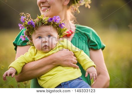 Happy mother holding her adorable little baby boy on a summer meadow. Mother with kid in flower wreath. Family together parent with little child. Woman hugging baby on sunny day.
