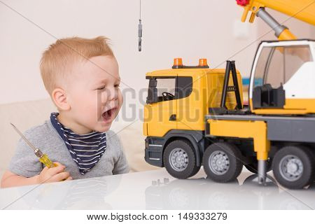 Portrait of adorable smiling toddler boy sitting at the table playing with a big construction car at home. Little child with toy car. Educative toys for children. Early learning and developing concept