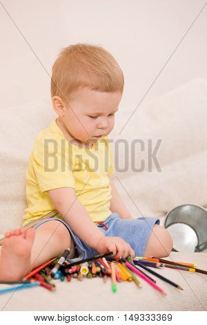 Cute little toddler boy in yellow shirt sitting on the sofa and playing with colorful pencils. indoors. child having fun. Early learning. Creative. Toddler going to draw