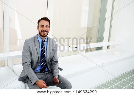 Smiling man manager with portable touch pad in hands is sitting in modern office interior before meeting with boss. Cheerful male skilled economist dressed in luxury suit is posing during work break