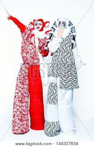 Two cheerful female clowns dressed in black and white cloth on a white background