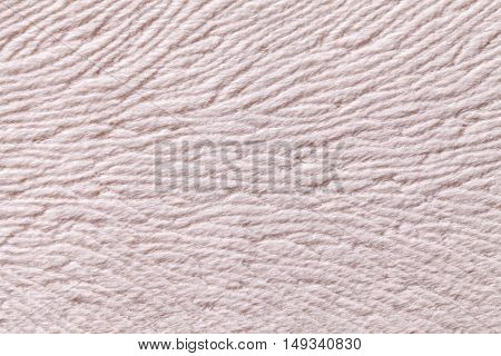 Light beige background from a soft wool textile material closeup. Fabric with natural texture. Cloth backdrop.