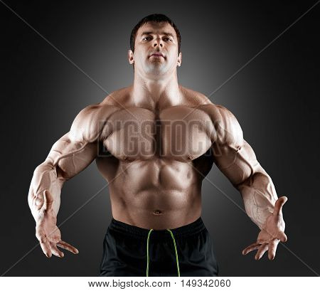 Handsome muscular bodybuilder posing over black background. Concept of the sport, strong, healthy lifestyle and nutrition. Isolated with clipping path.