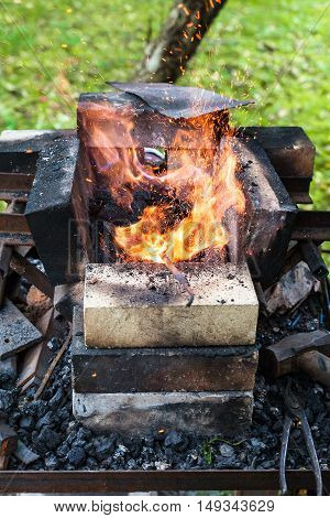 iron rod is heated in outdoor rural brick forging furnace in burning coals