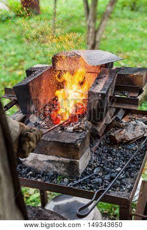 Blacksmith Heats Iron Rod In Forging Furnace