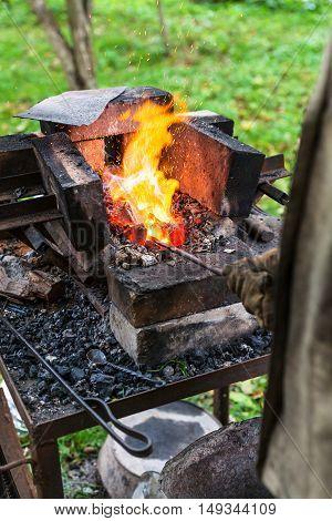 Blacksmith Heats Steel Rod In Forging Furnace