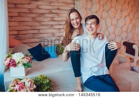 Young couple sitting embracing and having fun at home