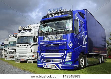 ALAHARMA FINLAND - AUGUST 12 2016: Blue Volvo FH Fierce Tiger of Lillbacka Logistics Oy in row of other show trucks on Power Truck Show 2016.
