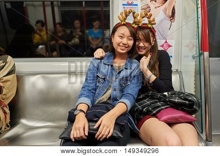 HONG KONG - 25 DECEMBER 2015: two women posing in MTR train. The Mass Transit Railway is the rapid transit railway system in Hong Kong. It is one of the most profitable systems in the world