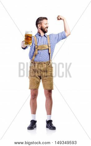 Handsome young man in traditional bavarian clothes, holding a mug o beer, showing biceps on his arms. Oktoberfest. Studio shot on white background, isolated.