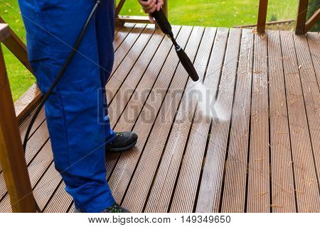 cleaning wooden terrace with high pressure washer