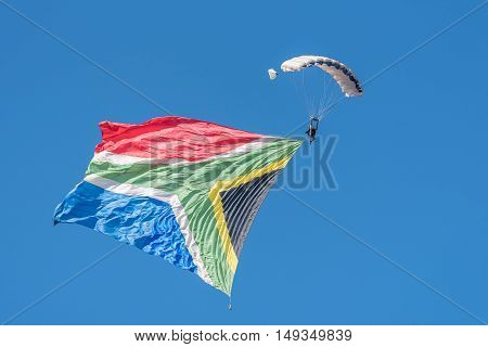BLOEMFONTEIN SOUTH AFRICA - JULY 16 2016: An unidentified skydiver with a big South African flag in a public display at the Tempe Airport at Bloemfontein
