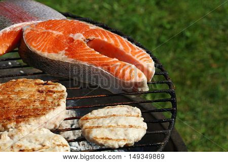 Chicken Or Turkey Burgers And Salmon Fish On Grill