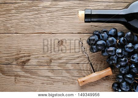 Wine bottle corkscrew and grape on wooden table top view