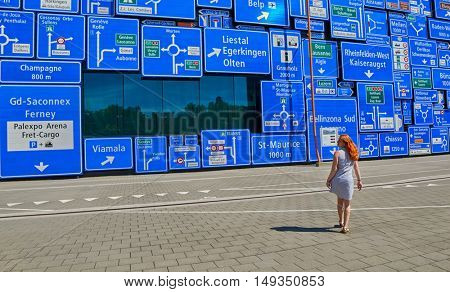 LUZERN, SWITZERLAND - 10 August 2016: Woman lost her way against a wall with a lot of road signs