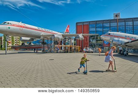 LUZERN, SWITZERLAND - 10 August 2016: Family enjoying scooter ride in Swiss Museum of Transport with Swiss Air Vintage airplanes in their back