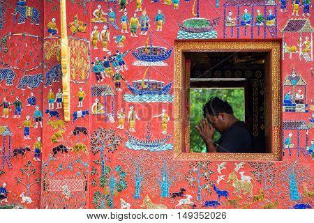 LUANG PRABANG, LAOS - JUNE 9, 2015 : tourist is prying for Buddha at wat Xieng Thong in Luang Prabang , Laos