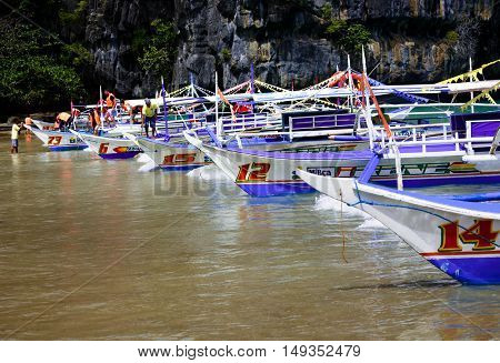 PALAWAN PHILIPPINES FEBRAURY 11 2016, Longtail boats line the beach near the cave entrance of Puerto Princesa subterranean underground river - One of the 7 New Wonders of Nature