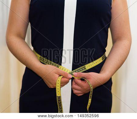 Closeup womans stomach wearing blue dress, holding measure band between hands, weightloss concept.