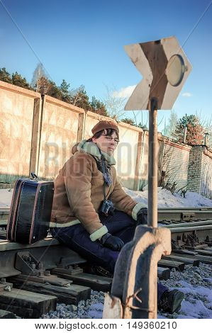 Serious young man in a sheepskin coat and beret with a suitcase and a camera sitting on the rails near the sign of railway switch in winter day.