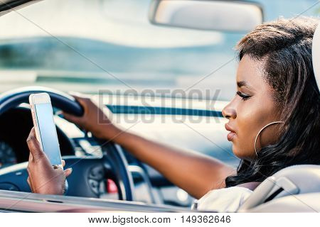 Close up portrait of young african female driver typing on smart phone while driving.