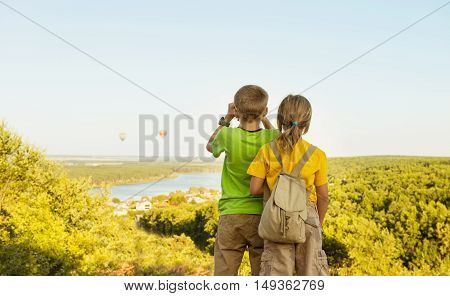 Childhood travelling friendship and dream concept. Two little children tourists looking into the distance on hot-air balloons summer evening.