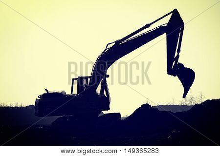 Silhouette excavator on a construction site digging
