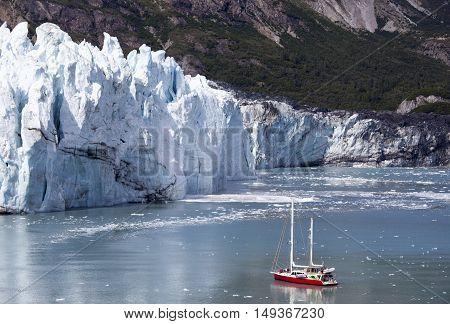 Small tourist boat getting closer to the glacier in Glacier Bay national park (Alaska).