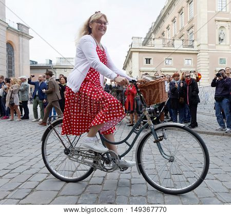 STOCKHOLM - SEPT 24 2016: Smiling woman wearing red dress cycling on old fashined bicycle in the Bike in Tweed event September 24 2016 in Stockholm Sweden