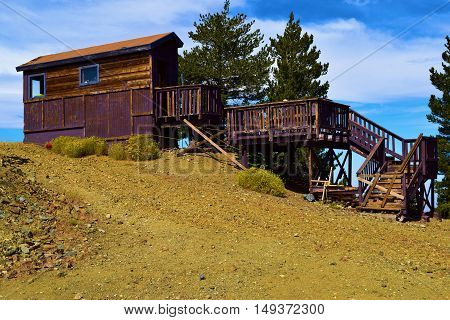 Rustic wooden building which needs maintenance surrounded by Pine Trees taken in Mt Baldy, CA