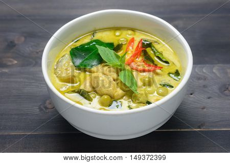 green curry with chicken (Kang Keaw Wan Gai) on wooden background Thai local food