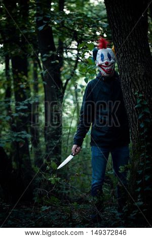 scary clown with big knife in wood