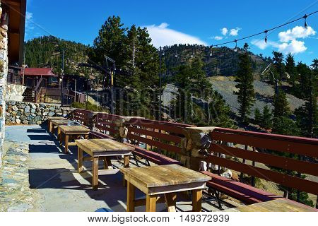 September 26, 2016 in Mt Baldy, CA:  Outdoor courtyard patio seating with wooden furniture creating a rustic vibe taken at the Mt Baldy Notch Lodge where people can dine with spectacular views of mountain scenery in Mt Baldy, CA