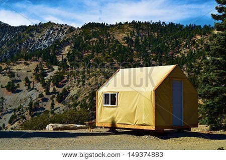 Modern rustic style tent cabin where people can enjoy a comfortable camping experience taken at a forest in Mt Baldy, CA