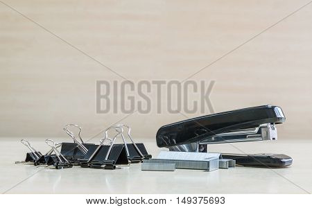 Closeup black stapler and black stamp paper clip office equipment on blurred wood desk and wall in office room textured background under window light