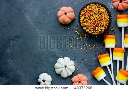 Candy corn marshmallow pops sugar sprinkling and candy pumpkin - Halloween party or thanksgiving concept background with copy space