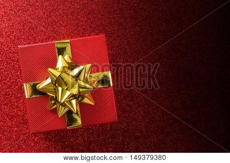 Red Gift On Bright Red Textured Table Top View