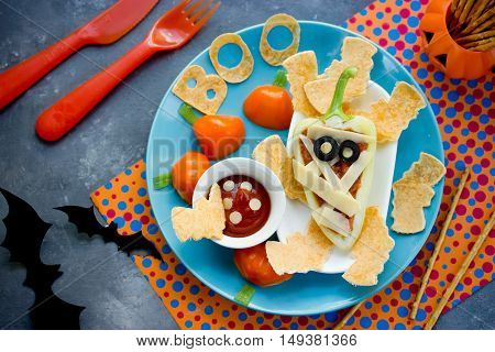 Fun food art idea for baby food - stuffed bell pepper mummy with sauce and tortilla crisps. Halloween food recipe top view