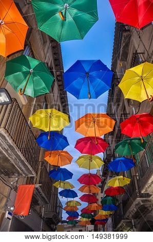 Antique Bystreet Decorated With Colored Umbrellas.
