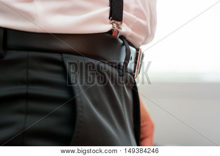 Closeup of belt with suspenders. Groom ready for ceremony.