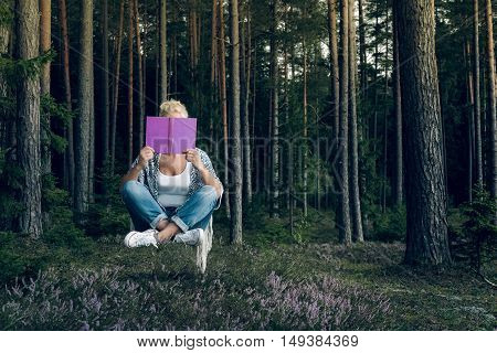 Young beautiful woman reading a book and levitates in the forest. Relaxed lifestyle.