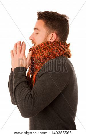 Man With Flu And Fever Wrapped In Scarf Holding Cup Of Healing Tea And Coughing.