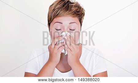 Short haired woman blowing her nose on the white background. Seasonal diseases. Allergies. Cold in the head. Sneeze.