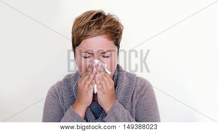 Short haired woman wearing a sweater blowing her nose on the white background. Seasonal diseases. Allergies. Cold in the head. Sneeze.