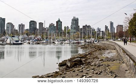 Stanley Park, Vancouver, BC - April 21, 2015 - view of Vancouver from seawall at Stanley Park with the water level low.  Looking at the marina filled with yatchs and sailboats on a bright slightly overcast day with reflections.
