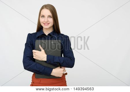 Portrait of smiling business woman with pen and paper folder. Young pretty worker writing something in her papers