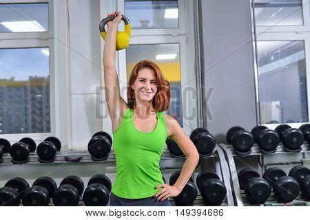 Fitness, sport, exercising lifestyle - middle age athletic woman pumping up muscules with dumbbell.