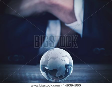 Businessman with world glass sphere with continents on the table